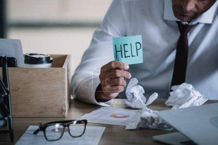 Photo pour Vue recadrée de l'homme d'affaires bouleversé retenant la note collante avec le lettrage d'aide près de la table - image libre de droit