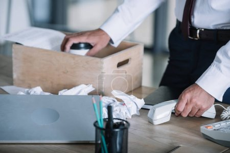 Photo for Cropped view of man holding paper cup near wooden box and crumpled paper balls on table - Royalty Free Image