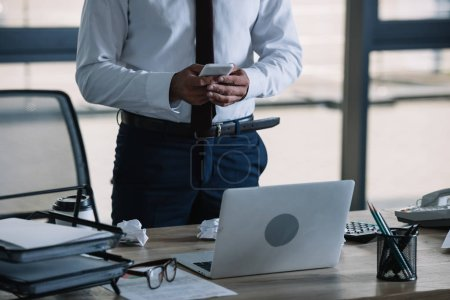 Photo for Cropped view of businessman using smartphone near laptop in office - Royalty Free Image