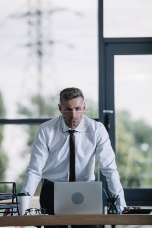 Photo for Serious businessman in formal wear standing near desk and looking at camera - Royalty Free Image