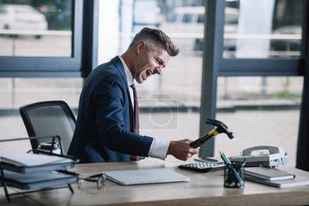 Photo pour Foyer sélectif de l'homme d'affaires fâché retenant le marteau près du téléphone rétro dans le bureau - image libre de droit