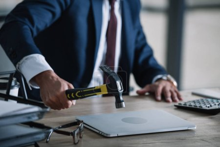 Photo for Cropped view of businessman holding hammer near laptop in office - Royalty Free Image