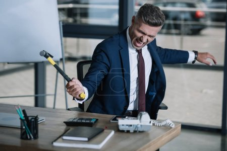 Photo for Selective focus of angry businessman holding hammer near table - Royalty Free Image