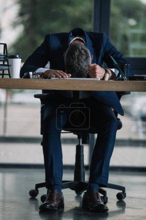 Photo pour Homme s'asseyant près du bureau avec la cuvette de papier dans le bureau moderne - image libre de droit