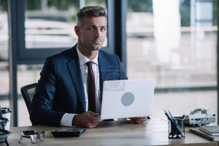 Photo pour Homme d'affaires beau retenant l'ordinateur portatif et regardant l'appareil-photo - image libre de droit