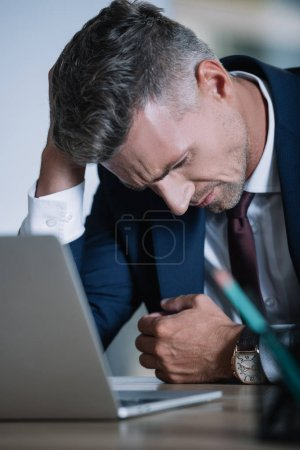 Photo for Selective focus of frustrated businessman in formal wear near laptop in office - Royalty Free Image