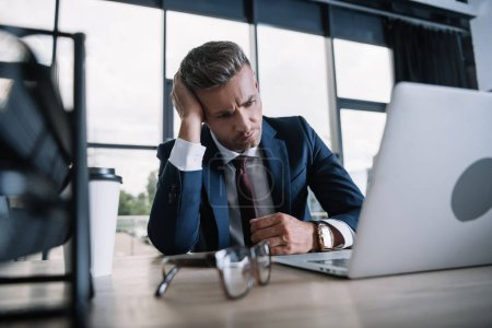 selective focus of frustrated man looking at laptop in office