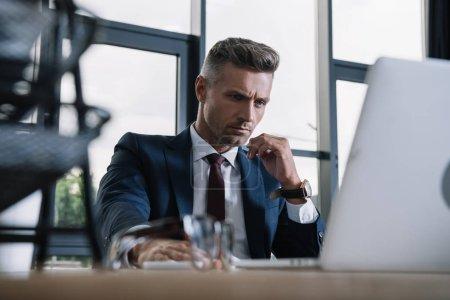Photo pour Foyer sélectif de l'homme d'affaires en utilisant un ordinateur portable dans le bureau moderne - image libre de droit