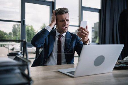 Photo pour Foyer sélectif de l'homme d'affaires étonné utilisant le smartphone près de l'ordinateur portatif dans le bureau - image libre de droit