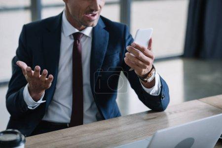 Photo pour Vue recadrée de l'homme d'affaires surpris à l'aide d'un smartphone et geste près d'un ordinateur portable - image libre de droit