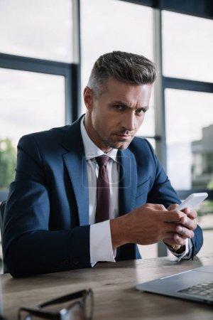 Foto de Enfoque selectivo de apuesto hombre de negocios sosteniendo teléfono inteligente y mirando la cámara - Imagen libre de derechos