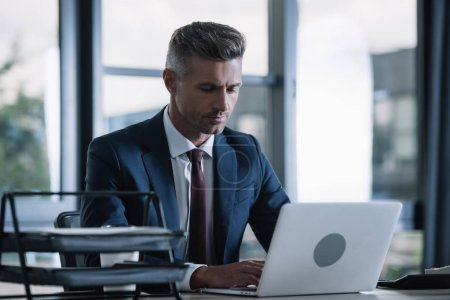 Foto de Enfoque selectivo de hombre de negocios guapo en ropa formal usando portátil en la oficina - Imagen libre de derechos