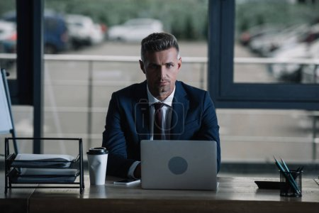 Photo for Handsome businessman looking at camera near laptop and paper cup - Royalty Free Image