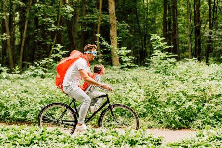 Photo for Side view of father and son riding bicycle around forest - Royalty Free Image