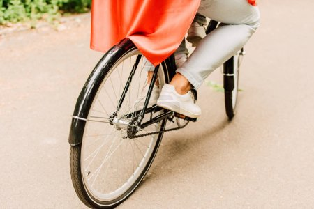Photo for Cropped view of dad with son in red cloak riding bicycle - Royalty Free Image