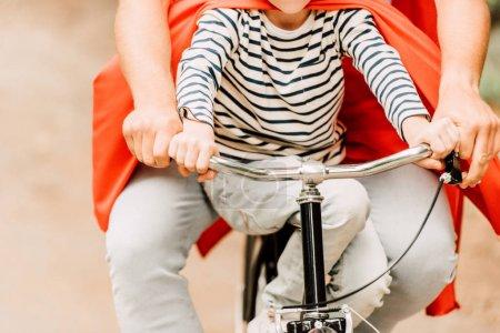 Photo pour Vue recadrée de père avec des manteaux rouges de fils sur le vélo - image libre de droit