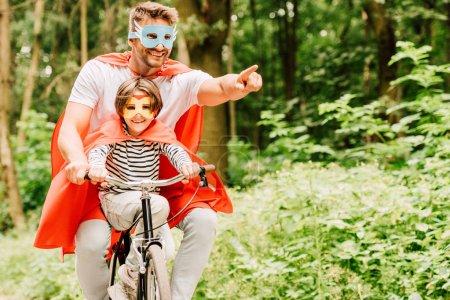 Vater und Kind radeln in Superheldenkostümen durch den Wald