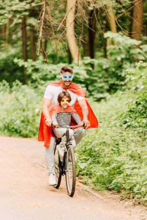Ganzkörperansicht von Vater und Kind beim Fahrradfahren im Wald in Superheldenkostümen