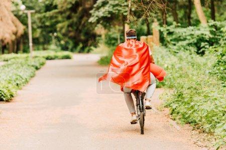 Photo pour Vue arrière du père et du fils conduisant le vélo dans les manteaux rouges - image libre de droit