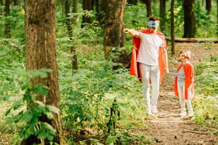 Foto de Vista completa de padre e hijo de pie en trajes de superhéroes en el bosque, mientras que papá apuntando con el dedo - Imagen libre de derechos