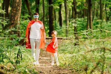 Foto de Vista completa de padre e hijo de pie en trajes de superhéroes en el bosque - Imagen libre de derechos