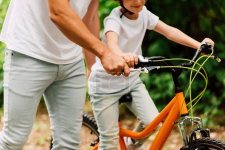 Photo for Cropped view of son riding bicycle and father holding handles to help child to ride - Royalty Free Image