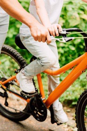 Photo pour Vue recadrée de la poignée de fixation de père du vélo pour aider le fils à monter - image libre de droit
