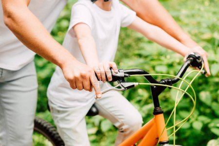 Photo for Cropped view of father and son holding handles of bicycle while boy riding - Royalty Free Image