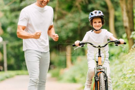 Photo for Cropped view of father cheering son while boy riding bicycle and looking at camera - Royalty Free Image