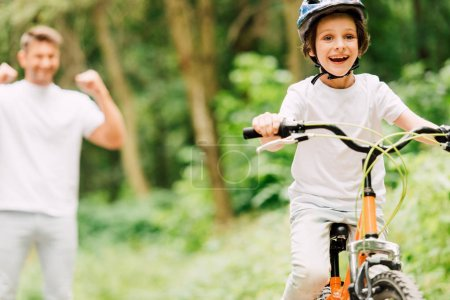 selective focus of father cheering son while boy riding bicycle and looking at camera