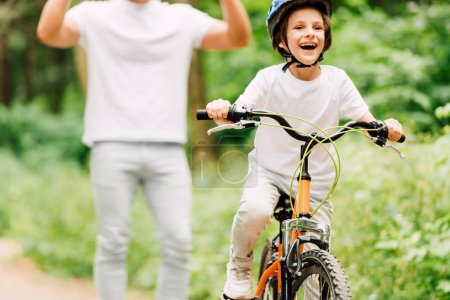 Photo for Cropped view of cheering son while boy riding bicycle and looking away - Royalty Free Image