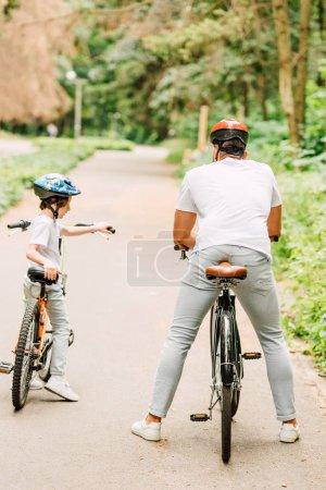 Photo pour Vue arrière du père avec son fils assis sur des vélos près de la forêt - image libre de droit