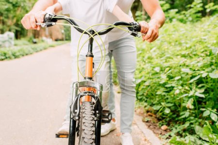 Photo pour Vue recadrée du garçon assis sur un vélo et du père tenant des poignées - image libre de droit