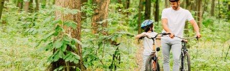 Photo pour Plan panoramique de père et fils marchant à bicyclette en forêt - image libre de droit