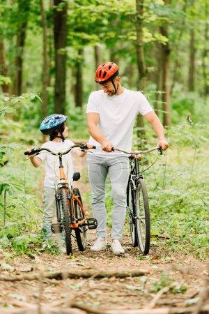 Ganzkörperansicht von Vater und Sohn beim Spazierengehen mit Fahrrädern im Wald