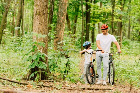 Photo for Full length view of father and son in helmets walking with bicycles in forest - Royalty Free Image
