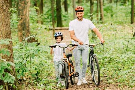 Ganzkörperansicht von Vater und Sohn, die mit Fahrrädern im Wald spazieren gehen und in die Kamera schauen