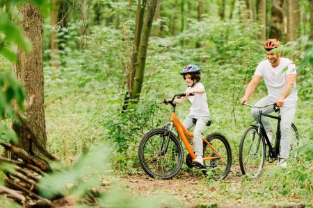 Photo for Selective focus of father and son in helmets riding bicycles around forest - Royalty Free Image