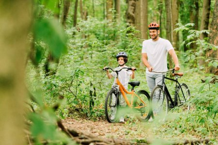 selective focus of father and son walking with bicycles in forest