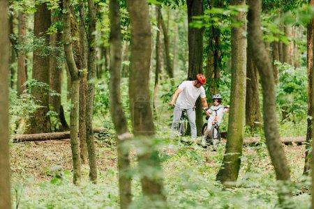 Photo pour Foyer sélectif du père et du fils dans les casques de vélo d'équitation dans la forêt - image libre de droit