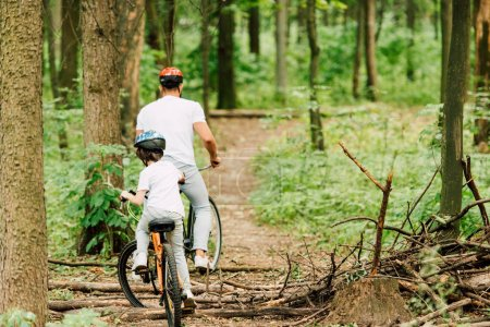 Photo for Full length view of father riding above fallen brunches and son riding after dad - Royalty Free Image
