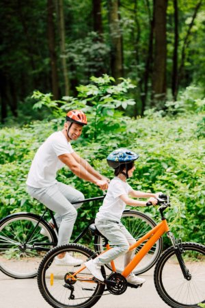 full length view of father and son riding bicycles on road near forest  while father looking at kid