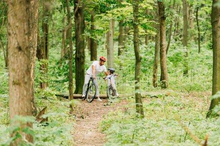 Photo pour Pleine longueur vue de père et fils debout dans la forêt tandis que l'homme parlant au garçon - image libre de droit