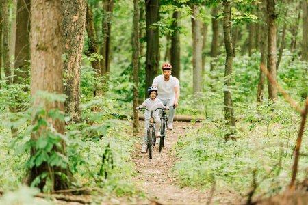 Photo pour Pleine longueur vue de père et fils chevauchant sur le chemin dans la forêt - image libre de droit