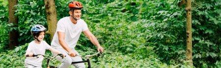 Photo pour Prise de vue panoramique du père et du fils souriant en vélo dans la forêt - image libre de droit