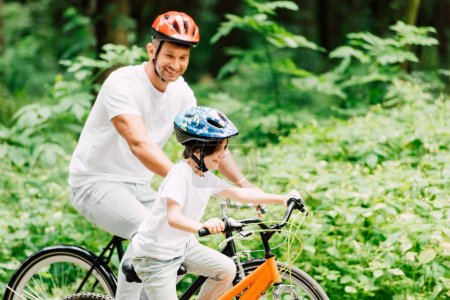 Photo for Father and son riding bicycles while dad looking at kid - Royalty Free Image