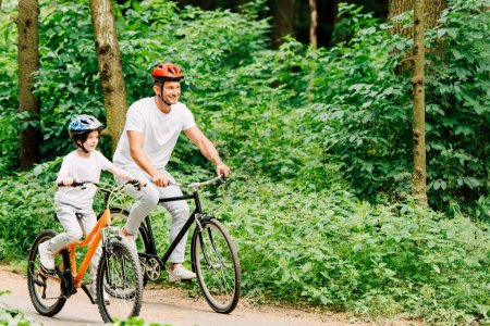 Photo for Father and son smiling while riding bicycles around forest - Royalty Free Image