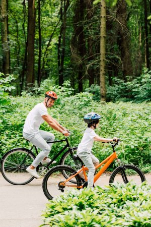 full length view of father and son riding bicycles while dad looking at boy bicycle wheel