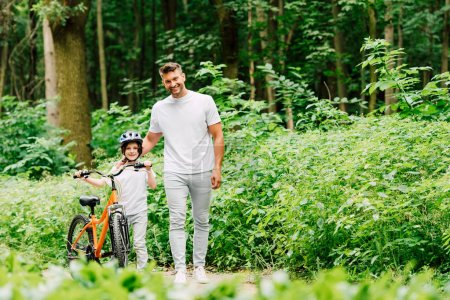 Ganzkörperansicht von Vater und Sohn, die stehen und in die Kamera schauen, während Junge Fahrrad hält