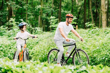 Photo for Selective focus of father and son smiling while riding bicycles in forest - Royalty Free Image